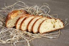 Gesneden wit brood die in stro op grijs linnentafelkleed liggen Royalty-vrije Stock Foto's