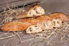 Gesneden wit brood die in stro op grijs linnentafelkleed liggen Stock Afbeelding