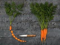 Gesneden wortelen, mes en een bos van wortelen op een donkere rustieke lijst De mening vanaf de bovenkant Vlak leg Stock Foto