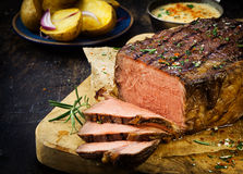 Gesneden zeldzaam braadstukrundvlees dat met kruiden wordt gekruid Royalty-vrije Stock Afbeeldingen