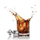 Geïsoleerder plons van kola in glas met ijsblokjes Stock Afbeelding