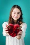 geïsoleerdn op witte, selectieve nadruk Mooie jonge glimlachende vrouw met gift in vorm van hart Stock Afbeeldingen