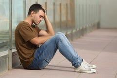 Gesorgtes Sitzen des Jugendlichen Junge auf dem Boden lizenzfreie stockbilder