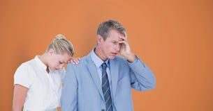 Gespannen bedrijfsmensen over oranje achtergrond Royalty-vrije Stock Foto's