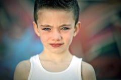 Gespannen jongen tegen graffitimuur Stock Afbeeldingen
