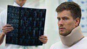 Gespannen mens die in schuim cervicale kraag op x-ray resultaat, slechte diagnose wachten stock videobeelden