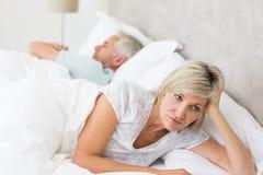 Gespannen vrouw die naast de mens in bed liggen Stock Foto's