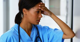 Gespannen vrouwelijke arts die zich in gang bevinden stock footage