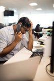 Gespannen zakenman die op landlijn bij bureau spreken Stock Foto