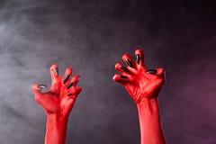 Gespenstische Hände des roten Teufels mit schwarzen glatten Nägeln Stockfoto