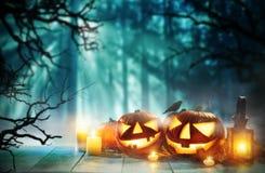Gespenstische Halloween-Kürbise auf hölzernen Planken Stockbilder