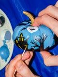 Gespenstische Halloween-Szene, die auf kleinem Kürbis gemalt wird Stockfoto