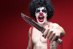Gespenstischer Clown Holding ein blutiges Messer Stockfoto