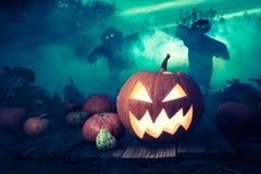 Gespenstischer Halloween-Kürbis auf Dunkelfeld mit Vogelscheuchen Lizenzfreies Stockfoto