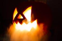 Gespenstischer Halloween-Kürbis mit dem Rauche auf dem schwarzen Hintergrund Lizenzfreies Stockfoto