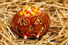 Gespenstischer Kürbis füllte mit Süßigkeitsmais auf Stroh Stockfotografie