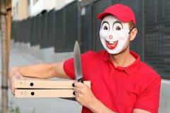 Gespenstischer Pizzalieferungskerl mit einem Messer lizenzfreies stockfoto
