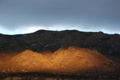 Gespenstisches Sonnenlicht bei Sonnenuntergang auf den Sandia-Bergen lizenzfreie stockfotos