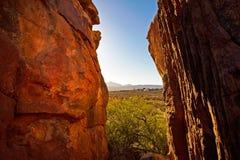 Gespleten tussen rode rotsen die vallei overzien stock afbeeldingen