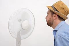 Gespoelde mens die heet voor een ventilator voelen royalty-vrije stock afbeelding
