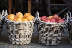 Gesponnene Körbe mit roten Äpfeln und Orangen stockfotos