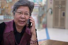 Gespräch der älteren Frau am Handy im Kaufhaus älterer F.E. Lizenzfreie Stockfotos