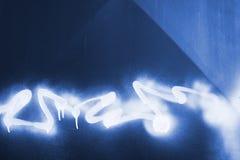 Gesprühte Graffiti auf blauem Metall Lizenzfreies Stockfoto