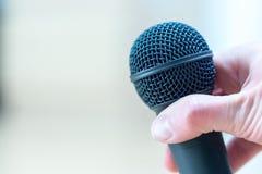 Gesprek: De journalist houdt een microfoon in zijn hand Sluit omhoog stock foto