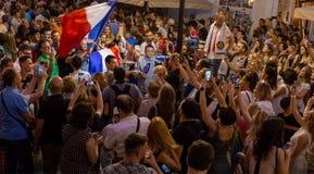 Gesprek op de straat De voetbalfans van verschillende landen vieren de overwinning van het Franse team Stock Fotografie