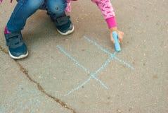 Gesso caucasico piacevole di tiraggio della bambina su attività di Parenting di Asphalt Lines Blue Chalk Educative per i bambini  fotografia stock