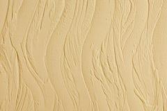 Gesso decorativo. Struttura dello stucco della parete. Nelle onde di stile, colore beige. Fotografia Stock