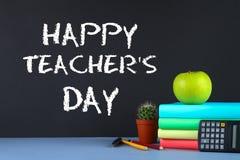 Gesso del testo su una lavagna: Il giorno dell'insegnante felice Rifornimenti di scuola, ufficio, libri, mela Fotografia Stock Libera da Diritti