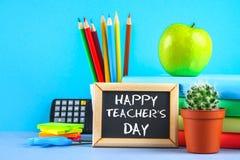 Gesso del testo su una lavagna: Il giorno dell'insegnante felice Rifornimenti di scuola, ufficio, libri, mela Fotografia Stock