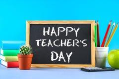 Gesso del testo su una lavagna: Il giorno dell'insegnante felice Rifornimenti di scuola, ufficio, libri, mela Immagini Stock