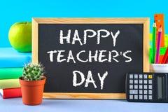 Gesso del testo su una lavagna: Il giorno dell'insegnante felice Rifornimenti di scuola, ufficio, libri, mela Immagine Stock