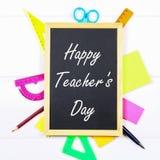 Gesso del testo su una lavagna: Il giorno dell'insegnante felice Rifornimenti di scuola, ufficio, libri, mela Immagini Stock Libere da Diritti