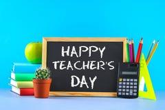 Gesso del testo su una lavagna: Il giorno dell'insegnante felice Rifornimenti di scuola, ufficio, libri, mela Fotografie Stock Libere da Diritti