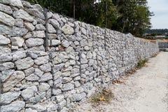 A gestão da retenção da inclinação com rochas e a rede de arame prendem o sistema Fotografia de Stock