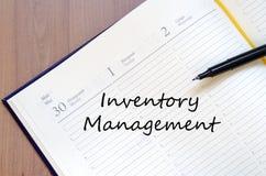 A gestão de inventário escreve no caderno fotos de stock