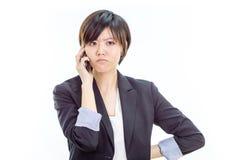 Gestörte asiatische Geschäftsfrau am Handy lizenzfreie stockfotografie