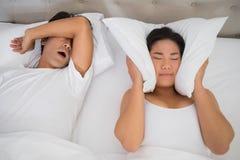 Gestörte Frau, die ihre Ohren mit Kissen bedeckt, um heraus schnarchen zu blockieren Lizenzfreie Stockbilder