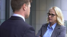 Gestörte Geschäftsfrau, die männliche Firmenarbeitskraft, Unternehmensunterordnung schilt stock footage