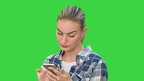 Gestörte lesende schlechte Textnachrichten der Frau am Telefon, das ihren Kopf im Elend auf einem grünen Schirm, Farbenreinheits- stock video footage