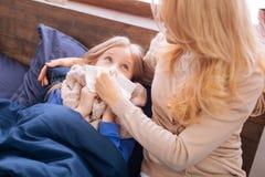 Gestörte Mama, die ihre Kindernase durchbrennt Lizenzfreies Stockbild