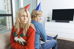 Gestörte Paare in den Weihnachtsstrickjacken und in Parteihüten, die zu Hause zurück zu Rückseite sitzen Lizenzfreies Stockfoto