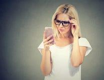 Gestörte umgekippte Frau in den Gläsern, die ihren Handy mit Frustration betrachten Stockfotografie