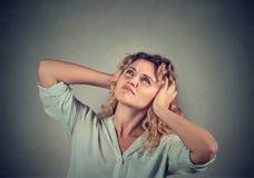 Gestörte, unglückliche, betonte Frau, die ihre Ohren, oben schauend bedeckt Stockbilder