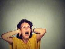 Gestörte unglückliche betonte Frau, die ihre Ohren, oben schauend bedeckt und schreien Stockfotografie
