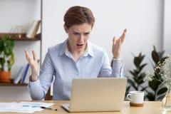 Gestörte verärgerte Geschäftsfrau, die den Laptop frustriert über defekten Computer betrachtet lizenzfreie stockfotos