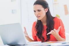 Gestörter Designer, der vor ihrem Laptop gestikuliert Lizenzfreie Stockbilder